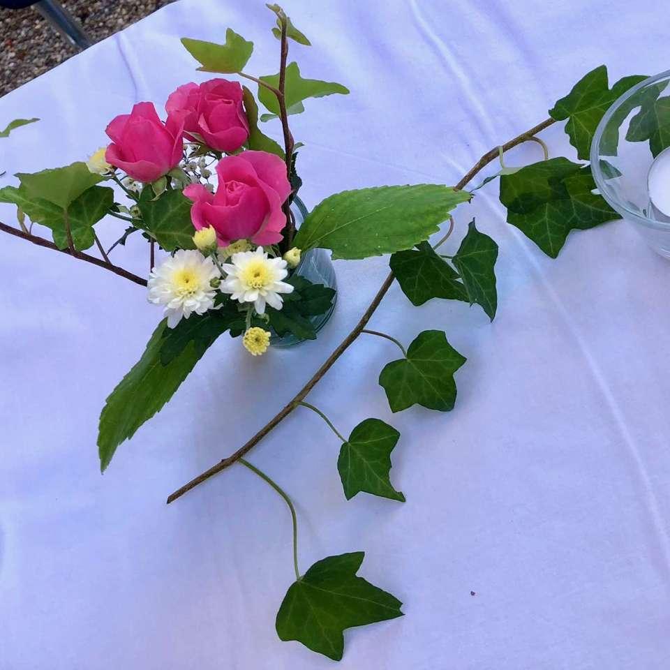Tischdekoration mit Blumen und Efeu